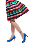 Women's multicolored dress and legs in blue high heels. Women's multicoloured dress and legs in blue high heels and drum kit tattoo on leg royalty free stock photo