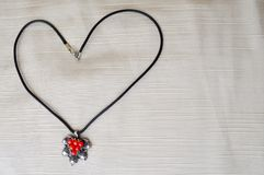 Women`s necklace with a silver pendant with red circles in the form of a heart made of black thread. On a beige background Royalty Free Stock Images