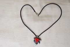 Women`s necklace with a silver pendant with red circles in the form of a heart made of black thread Stock Photos