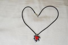 Women`s necklace with a silver pendant with red circles in the form of a heart to the day of St. Valentine made of black thread Stock Images