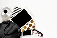 Women`s office desk on white background touch pad tablet gadget cellphone with gold stylish books black handbag, top Stock Photography