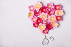 Women`s perfume bottle and pink mallow flowers. Minimalism beauty concept.  Royalty Free Stock Image