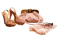 Women`s pink accessories on white background.Bag with gold detai. Ls and buckles, there are summer sandals with thin high heels and thick Golden soles, silk Stock Photo
