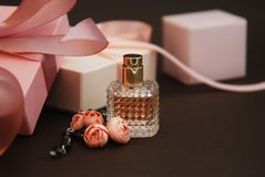 Women's Pink Perfume in Beautiful Bottle and Artificialt Flowers Bracelet on Brown Background with gift boxes on Background. Women's Pink Perfume in royalty free stock photo