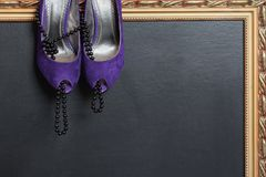 Women`s purple velvet shoes with high heels and black beads take shoes, on a dark background with a gold frame.  Stock Photo