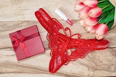 Women`s red butterfly strings, lipstick and bouquets of tulips. Set a date. Valentine`s Day royalty free stock photos