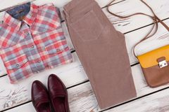 Women`s retro outfit. On wooden surface, top view. Western shirt, brown leather shoes, velvet pants and bag Stock Photos