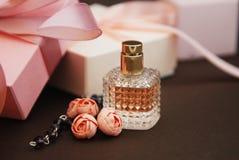 Women& x27; s Roze Parfum in Mooie Fles en Artificialt-Bloemenarmband op Bruine Achtergrond met giftdozen op Achtergrond Stock Fotografie