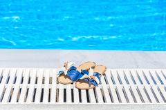 Women's sandals with a flower on the edge of the swimming pool Royalty Free Stock Photo
