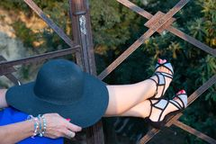 Close up of female legs with a wide brimmed black women`s hat. stock photo