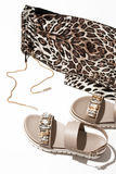 Women`s sandals and leggings. Beige women`s sandals with shiny crystals stand near pants with a leopard print, white background, sharp shadows Stock Photography