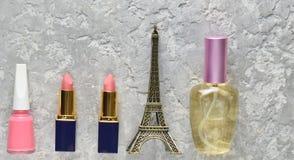 Women& x27; s schoonheidsmiddelen van Parijs Twee roze lippenstiften, een parfumfles, nagellak, een beeldje van de toren van Eiff royalty-vrije stock fotografie