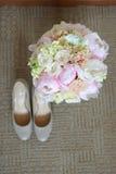 Women& x27; s-Schuhe mit Pfingstrosen auf dem Teppich Stockfoto