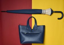 Women& x27;s seasonal accessories. Female leather bag and umbrella on a red yellow background. Top view. Flat lay. Women& x27;s seasonal accessories. Female Royalty Free Stock Photography