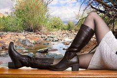 Women`s seasonal shoes. Girl shows high boots Royalty Free Stock Image