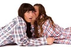 Women's secret. Two  beautiful women whisper secret Stock Images