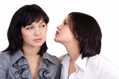 Women's Secret. Girl telling a secret to another - gossip isolated over a white background royalty free stock image