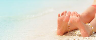 Women`s legs on the white sand beach summer vacation. Women`s legs on the beach. Beach travel concept royalty free stock photography