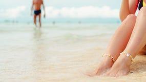 Women`s legs on the white sand beach summer vacation. Women`s legs on the beach. Beach travel concept stock photography