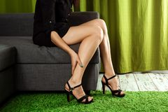 Women`s sexy legs. The girl holds her legs, the pain in her legs from the heels. Beautiful woman legs wearing dress with high hee. L shoes. The concept of leg stock photos