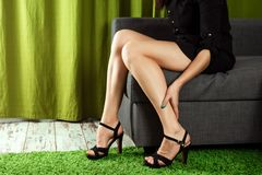 Women`s sexy legs. The girl holds her legs, the pain in her legs from the heels. Beautiful woman legs wearing dress with high hee. L shoes. The concept of leg stock photo