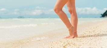 Women`s legs on the white sand beach summer vacation. Women`s legs on the beach. Beach travel concept royalty free stock images