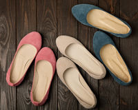 Women`s shoes ballerinas pink, blue and beige on a dark wooden royalty free stock images