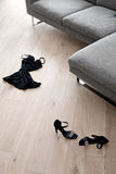 Women's shoes and clothes lying in front of a sofa Stock Photos