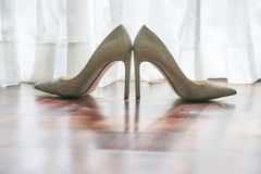 The women`s shoes on the wooden floor, the sun light behind the white curtain, the shadow of the shoes on the floor - low angle. The women`s shoes glittering on stock photography