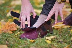 Woman taking adjusting her shoe royalty free stock photography