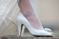Women's shoes and hem of wedding dress. Leg of the bride in a white shoe. Stock Images