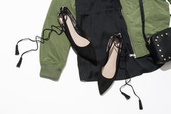 Women`s  shoes and jacket. Women`s black shoes near the green jacket and leather bag Stock Photos