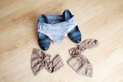 Women's shoes, panties and stockings lying on the floor Royalty Free Stock Image