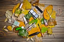 Women& x27; s-skönhetsmedel för smink, objekt för omsorg av spikar, och dofter ligger på en trätabell i gula höstsidor arkivfoton