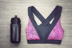 Women`s sports bra and Black Bicycle water bottle. Sport accessories and fashion. Royalty Free Stock Image