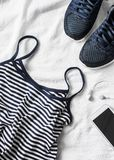 Women`s sports clothing on a light background. Sports women`s tank top with thin spaghetti straps, striped, running sneakers, ph. One, headphones. Top view Royalty Free Stock Photos