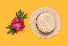 Women`s straw hat and beautiful pink flowers peonies on bright yellow background. Summer holiday background. Flat lay, top view, royalty free stock image