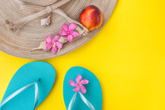 Women`s straw hat, pink tropical flowers, blue slippers, sea shells, nectarine on yellow background, beach vacation Stock Photo