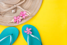 Women`s straw hat, pink tropical flowers, blue slippers, sea shells, on yellow background, beach vacation. Seaside, fashion, top view, copyspace Royalty Free Stock Photos