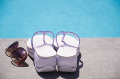 Women's stuff by the swimming pool. Women's flip flops and sunglasses by the swimming pool in sunny day Royalty Free Stock Photography