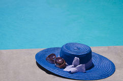 Women's stuff by the swimming pool. Women's summer heat and sunglasses by the swimming pool in sunny day Stock Images