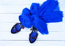 Women`s stylish sandals and a blue scarf. On a white wooden background. Flat lay Royalty Free Stock Image