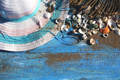 Women`s summer hat with a blue ribbon on a wooden background spr. Inkled with sand and shells stock photo