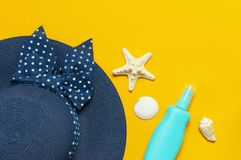 Women s summer straw hat, sunscreen bottle body spray shells starfish on yellow background top view flat lay copy space. Summer. Travel vacation concept. Summer royalty free stock photography