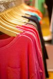 Women's t-shirts hanging in trendy boutique Royalty Free Stock Photos