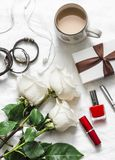 Women`s table beautiful background. Bouquet of roses, gift box, leather bracelets, lipstick, headphones, coffee on a light backgr. Ound, top view. Valentine`s stock photography