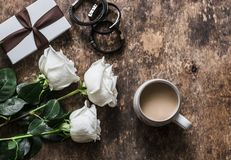 Women`s table. Bouquet of roses, gift box, leather bracelets, coffee on a dark wooden background, top view. Beauty concept stock image