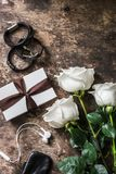 Women`s table. Bouquet of roses, gift box, leather bracelets, on a dark wooden background, top view, copy space for text. Beauty concept stock photography
