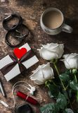 Women`s table. Bouquet of roses, gift box, leather bracelets, lipstick, headphones, coffee on a dark wooden background, top view. Valentine`s day background stock photos