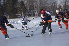 Women`s teams compete in a Pond Hockey Festival in Rangeley. Rangeley, Maine, USA - February 4, 2017: Women`s teams compete on the ice at the 11th annual New Stock Images